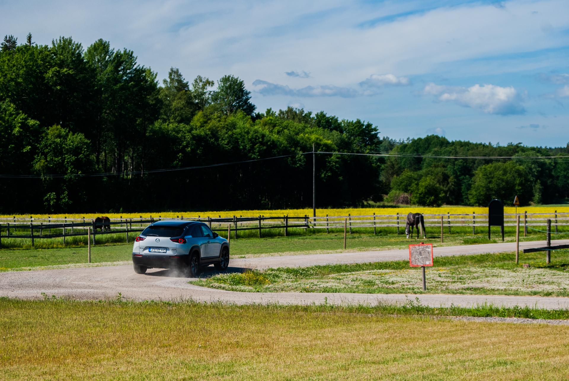 En vit Mazda MX-30 på en grusväg