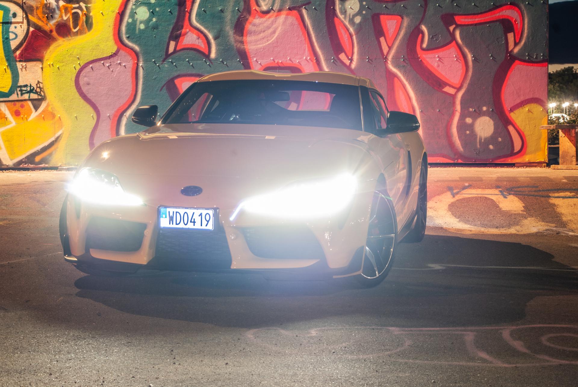 Gul Toyota GR Supra med strålkastarna på