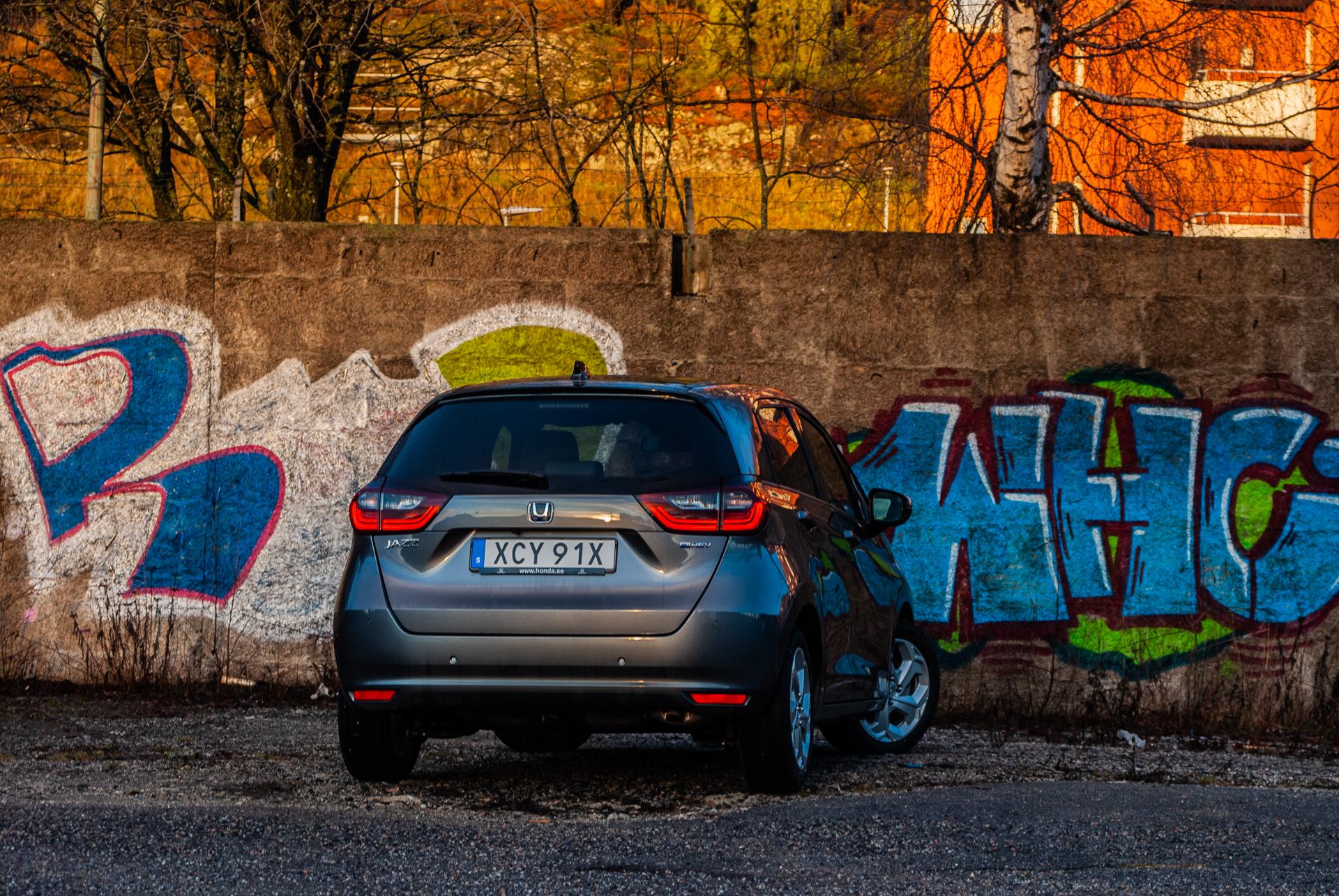 grå honda jazz vid graffitivägg